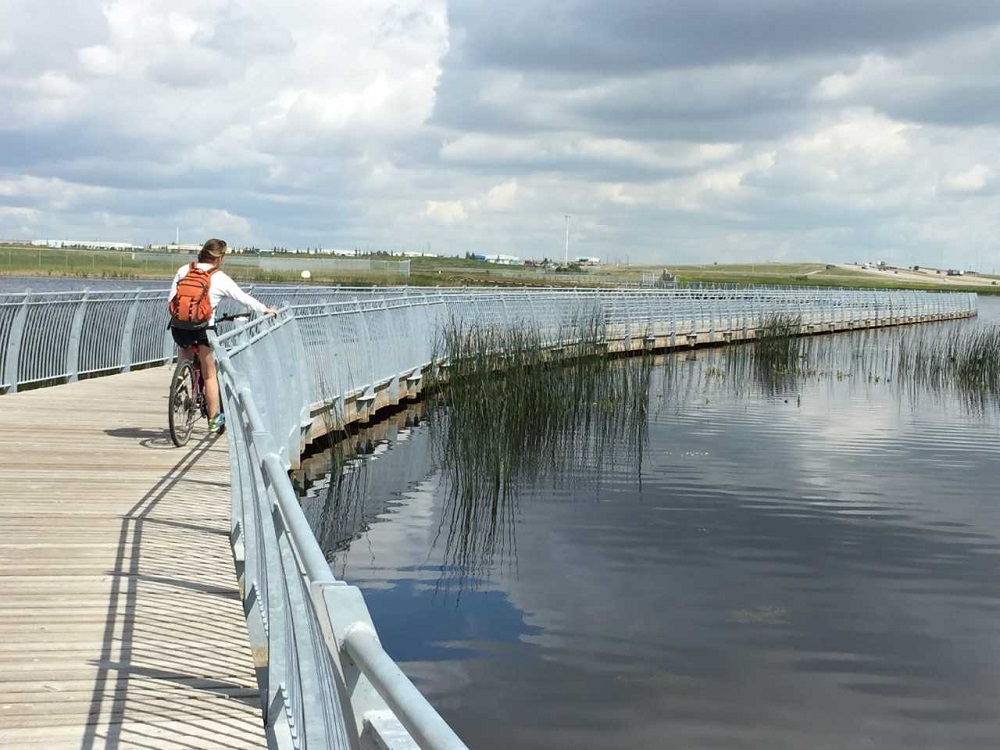 Cyclist on boardwalk over water