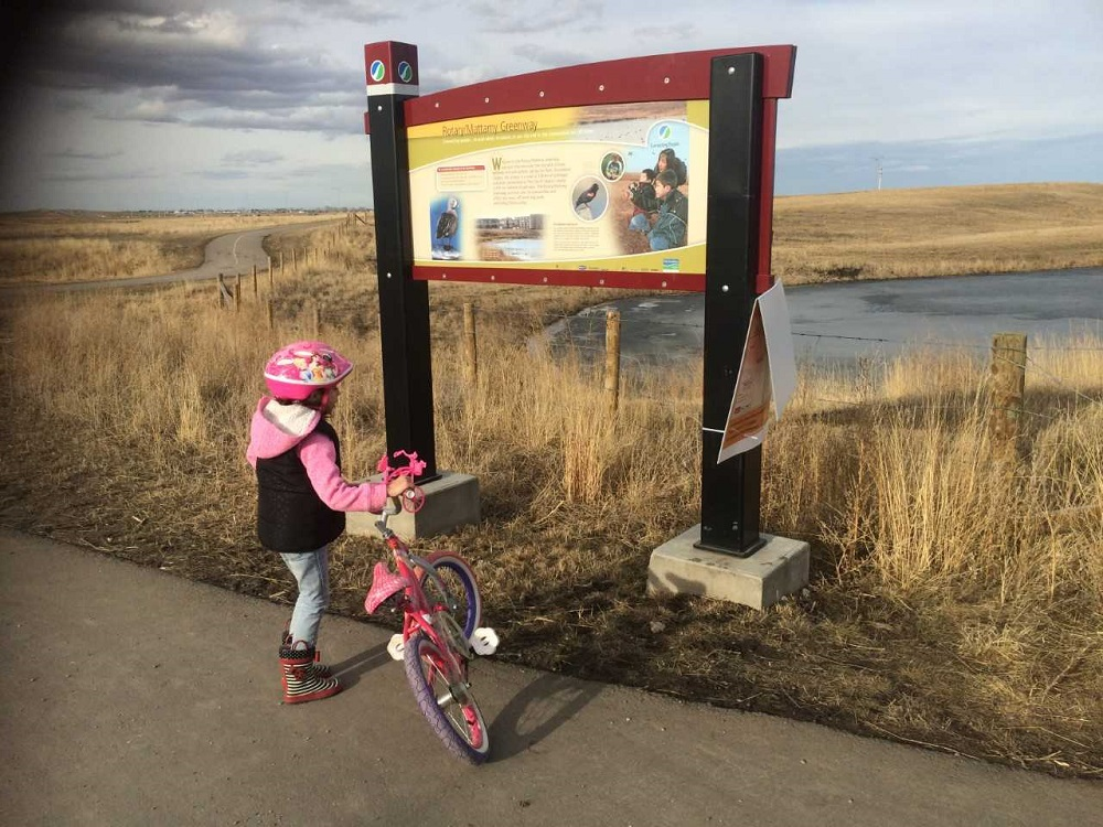 Child riding bike in front of nature trail sign