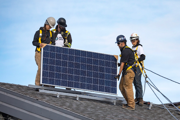Workers installing a solar panel on residence